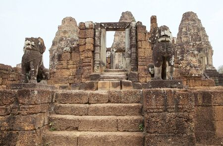 enclosing: The lion guardians at the East Mebon temple ruins, Angkor, Siem Reap, Cambodia. East Mebon temple was built in the second half of 10th century. Built in the general style of Pre Rup, East Mebon has two enclosing and three tiers. Stock Photo