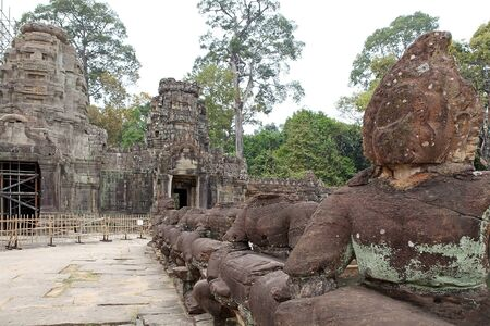 ar: The naga of the balaustraded causeway accross the moat to Preah Khan temple ruins, Angkor, Siem Reap, Cambodia. Preah Khan was built in the second half of 12th century. The temple is flat in design, with a basic plan of successive rectangular galleries ar