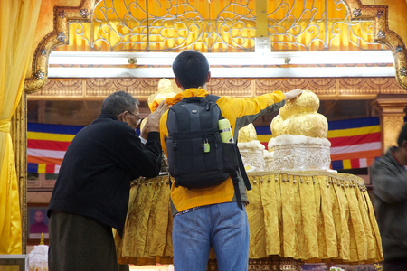 prying: Pilgrims are prying the Buddha images at the Phaung Daw Oo Pagoda, Lake Inle, Myanmar. Phaung Daw Oo Pagoda is a noteble buddhist site in Myanmar or Burma. The pagoda houses five small gilded images of Buddha, wich have been covered in gold leaf to the po