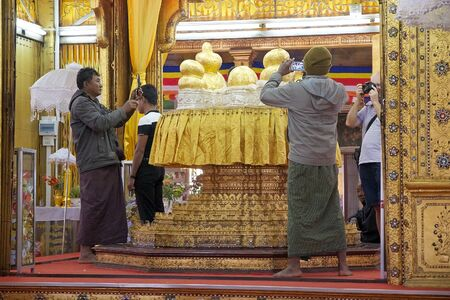 daw: Pilgrims and tourists are taking photographs of the Buddha image at the Phaung Daw Oo Pagoda, Lake Inle, Myanmar. Phaung Daw Oo Pagoda is a noteble buddhist site in Myanmar or Burma. The pagoda houses five small gilded images of Buddha, wich have been cov Editorial