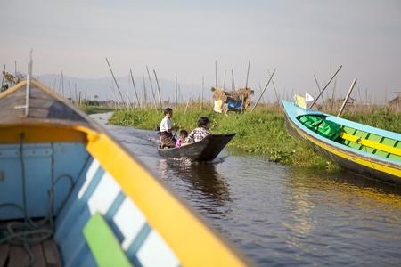 tierra fertil: Mujer birmana con ni�o va entre los jardines flotantes en barco tradicional en el lago Inle, Estado de Shan, Myanmar. Tradicional m�todo de la agricultura wich utiliza una peque�a �reas rectangulares de tierra f�rtil para cultivar en el lecho de un lago poco profundo