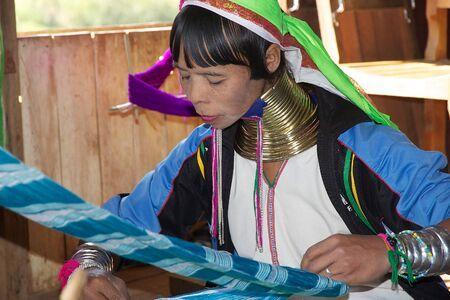 whose: Kayan Lahwi woman is weaving cotton and silk thread at the village of Nan Pan, Lake INle, Shan State, Myanmar. The Kayan is a subgroup of Red Karen, Tibeto-Burman minority of Burma. Kayan Lahwi is a group whose women wear the brass neck coils.