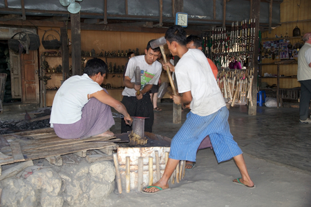 forge: Burmese men are forging a knife in a traditional forge at the Nan Pan village on the Lake Inle, Shan State, Myanmar Editorial