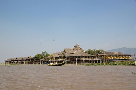 architecture bungalow: Traditional boat with tourists in front of traditional wooden stilt bungalows on the Lake Inle, Shan State, Myanmar.