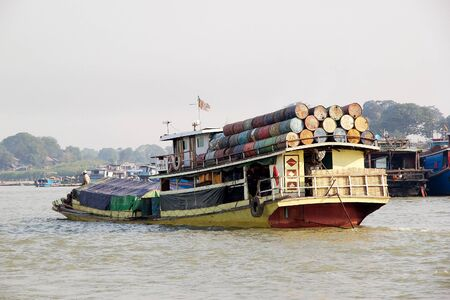 traditional goods: Traditional burmese boat is carrying goods on the Irrawaddy river at Mandalay, Myanmar. The Irrawaddy river flows from North to South through Burma. It is the countrys largest river and most important commercial waterway.