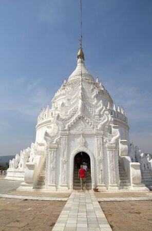 Tourists are visiting the Hsinbyume Pagoda also known as Myatheindan Pagoda. The Hsinbyume is a large white pagoda on the northern side of Mingun, Sangaing Region, Myanmar, on the western bank of Irrawaddy river. The pagoda is modeled on the Phisical desc