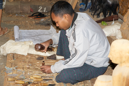 forsale: Burmese man is carving wood and making the image in the picture in Mandalay, Myanmar