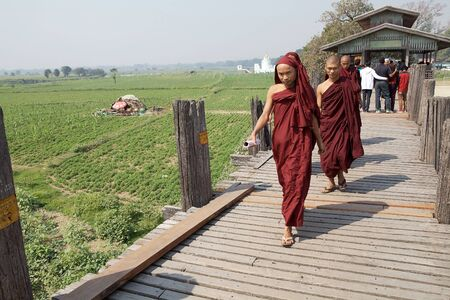robes: Buddhist monks in traditional robes are crossing the U Bein Bridge, Amarapura, Myanmar.  Editorial