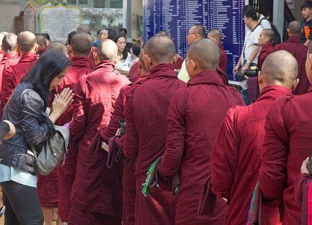 limosna: Monjes budistas en t�nicas tradicionales hacen limosna en la ma�ana en el Monasterio Mahagandayon en Amarapura, Mandalay, Myanmar.