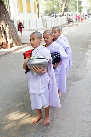 limosna: Young monks make alms in the early morning at the Mahagandayon Monastery in Amarapura, Mandalay, Myanmar.