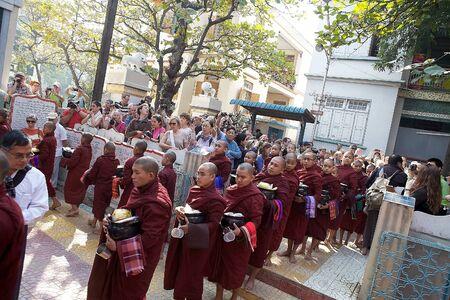 limosna: Monjes budistas en túnicas tradicionales hacen limosna en la mañana en el Monasterio Mahagandayon en Amarapura, Mandalay, Myanmar.