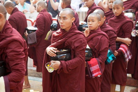 limosna: Buddhist monks in traditional robes make alms in the early morning at the Mahagandayon Monastery in Amarapura, Mandalay, Myanmar.