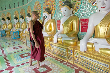 min: Buddhist monk is visiting the U Min Thonze Cave, Sagaing Hill, Myanmar. U Min Thonze Cave is a pagoda on the top of Sagaing Hill. U Min Thonze mean 30 caves. There are 45 Buddha images seated in a crescent shaped colonnade inside the pagoda