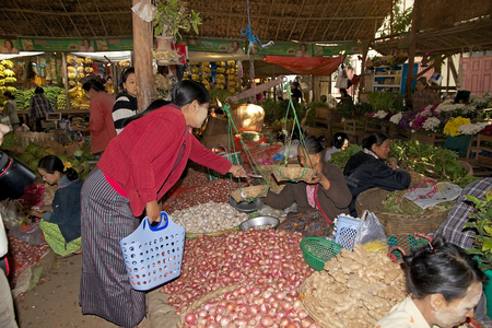 traditional goods: Burmese woman in traditional clothes is buying onions at the Nyang U market, Bagan, Myanmar. Located in the northeastern part of Bagan, Nyaung U market is Nyaung villages local market, where it is possible find goods in different section.