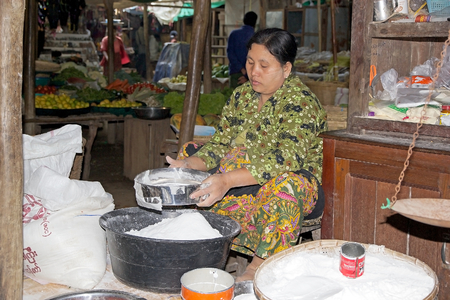 traditional goods: Burmese woman in traditional clothes is selling food at the Nyang U market, Bagan, Myanmar. Located in the northeastern part of Bagan, Nyaung U market is Nyaung villages local market, where it is possible find goods in different section.