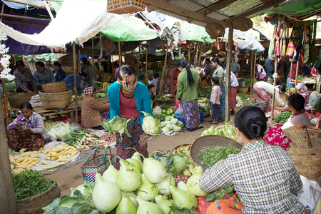 traditional goods: Burmese woman in traditional clothes is choosing vegetables at the Nyang U market, Bagan, Myanmar. Located in the northeastern part of Bagan, Nyaung U market is Nyaung villages local market, where it is possible find goods in different section.