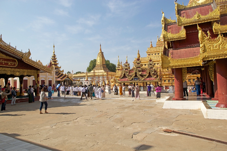 stu: Tourists and pilgrims are visiting the Shwezigon Pagoda, Nyaung U village, Bagan, Myanmar. Shwezigon Pagoda is a Buddhist temple ubicated in Nyaung U village, near Bagan. It is a prototype of a burmese stupas and consist of a circular gold leaf gilded stu Editorial