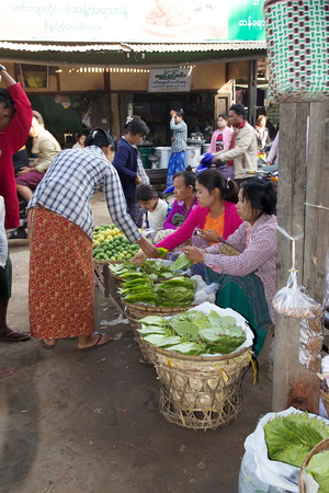 traditional goods: Burmese woman in traditional clothes is buying leaves for khat chewing at the Nyang U market, Bagan, Myanmar. Located in the northeastern part of Bagan, Nyaung U market is Nyaung villages local market, where it is possible find goods in different section