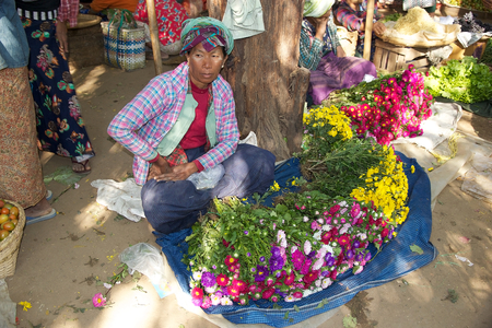 traditional goods: Burmese woman in traditional clothes is selling flowers at the Nyang U market, Bagan, Myanmar. Located in the northeastern part of Bagan, Nyaung U market is Nyaung villages local market, where it is possible find goods in different section.