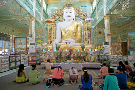 pone: Pilgrims are praying in front of the Buddha image at the Sone Oo Pone Nya Shin Pagoda, Nga Pa hill, Sagaing hill, Sagaing, Myanmar. Sone Oo Pone Nya Shin Pagoda lies on the top of Nga Pa hill, one of the 37 hilltop of Sagaing Hills. It was built in 674.