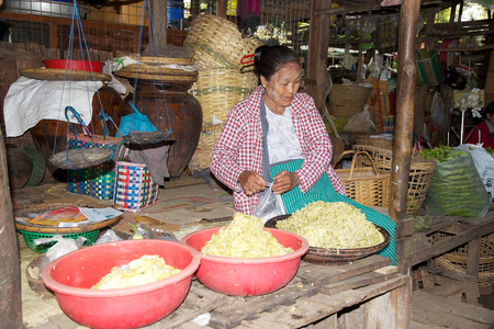 traditional goods: Burmese woman in traditional clothes is selling vegetables at the Nyang U market, Bagan, Myanmar. Located in the northeastern part of Bagan, Nyaung U market is Nyaung villages local market, where it is possible find goods in different section. Editorial