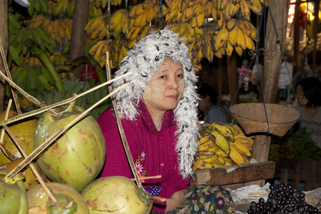 traditional goods: Burmese woman with traditional hat is selling fruits at the Nyang U market, Bagan, Myanmar. Located in the northeastern part of Bagan, Nyaung U market is Nyaung villages local market, where it is possible find goods in different section.