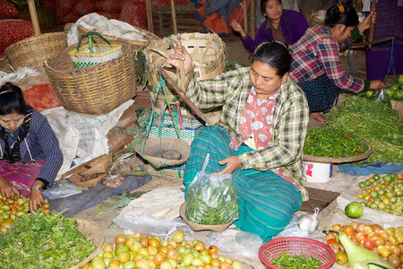 traditional goods: Burmese woman in traditional clothes is selling vegetables and fruits at the Nyang U market, Bagan, Myanmar. Located in the northeastern part of Bagan, Nyaung U market is Nyaung villages local market, where it is possible find goods in different section.