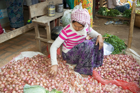 traditional goods: Burmese woman in traditional clothes is selling onions at the Nyang U market, Bagan, Myanmar. Located in the northeastern part of Bagan, Nyaung U market is Nyaung villages local market, where it is possible find goods in different section.