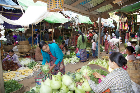 traditional goods: Burmese woman in traditional clothes is buying vegetables at the Nyang U market, Bagan, Myanmar. Located in the northeastern part of Bagan, Nyaung U market is Nyaung villages local market, where it is possible find goods in different section.