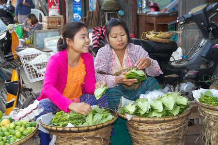 traditional goods: Burmese women in traditional clothes are selling leaves for khat chewing at the Nyang U market, Bagan, Myanmar. Located in the northeastern part of Bagan, Nyaung U market is Nyaung villages local market, where it is possible find goods in different secti Editorial
