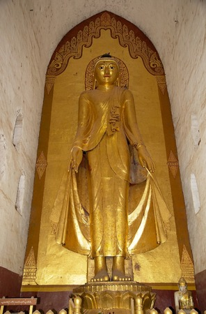 ful: Standing Buddha, East facing, adorned with gold leaf, at the Ananda Temple in Bagan, Myanmar. The Ananda Temple is a buddhist temple built in 1105 AD during the reign of King Kyanzittha. The temple was damaged in the heardquake of 1975 and it has been ful