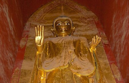 ful: Standing Buddha, West facing, adorned with gold leaf, at the Ananda Temple in Bagan, Myanmar. The Ananda Temple is a buddhist temple built in 1105 AD during the reign of King Kyanzittha. The temple was damaged in the heardquake of 1975 and it has been ful