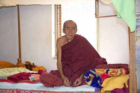 eligion: Old Buddhist monk with traditional robes in Bagan, Myanmar.