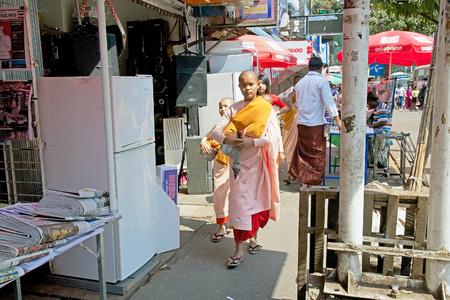 limosna: monástica femenina en el Budismo es hacer limosnas a lo largo de la calle en el centro de Yangon, Myanmar. Editorial