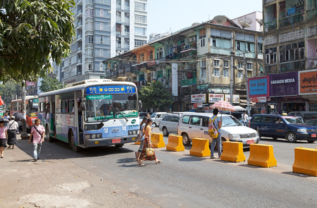milion: Bus along the street in downtown Yangon, Myanmar. Yangon, also known as Rangoon, is a former capital of Myanmar and the capital of Yangon region. It is the Countrys largest city and the most important commercial centre, with a population over five milion
