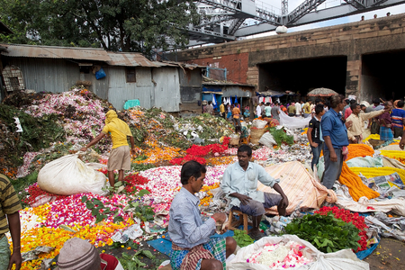 howrah: Indian men are selling flowers at the flower market in Kolkata, West Bengal, India. The Mullik Ghat, or Mallik Ghat, is near the southeast end of Howrah Bridge. The flower market is fascinatingly colorful virtually 24 hours a day. Editorial