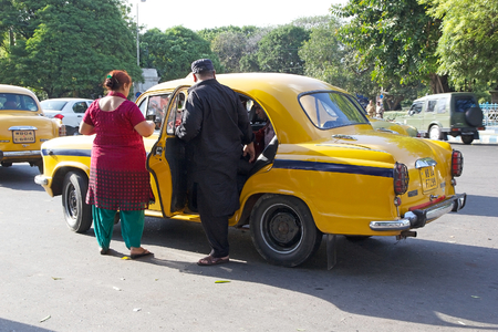 ambassador: Indian people are taking a taxi along the street in Kolkata, India. The metered-cabs are mostly of the brand Ambassador manufactured by Hindustan Motors, now out of production.