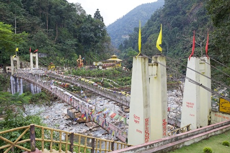 mahadev: The bridge with prayer flags over the Rangeet river with the Kirateshwar Mahadev Temple in the background, Legship, West Sikkim, India. The temple is a Hindu temple, identified to be a a Hindu pilgrimage site. Stock Photo
