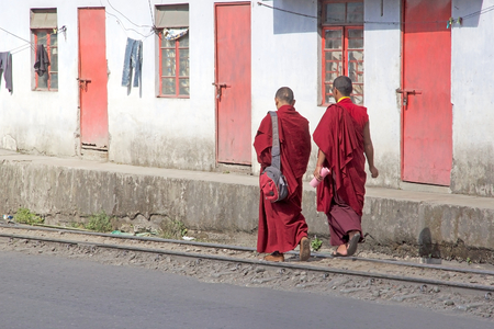 robes: Buddhist monks in traditional robes are walking along the 60 centimetre narrow-gauge Darjeeling Himalayan Railway in Dajeerling, West Bengal, India. Darjeeling Himalayan Railway run from Siliguri to Darjeeling. Estabilished in 1881, it was declared a Worl
