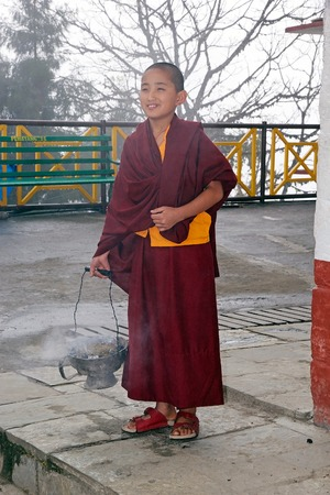 robes: Young Buddhist monk in traditional robes is carrying the fire for a ceremony at the Pemayangtse Monastery, Sikkim, India. Pemayangtse Monastery is a Buddhist monastery in Pemayangtse, near Pelling, Indian State of Sikkim. Founded by Lama Lhatsun Chempo in Editorial