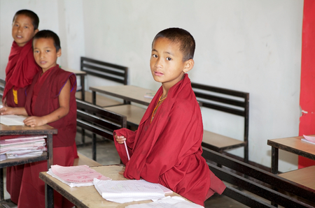 gompa: Sikkimese Buddhiost children in traditional robes in the classromm at the Labrang Gompa monastic school, Sikkim, India. The Labrang Gompa is a octagonal shape gompa along the road to Gagtok. The gompa was built as Buddhist ecclesiastical fortification. Editorial