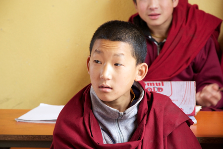 monastic: Sikkimese Buddhist child in traditional robes is attending a lesson in the classroom at the Labrang Gompa monastic school, Sikkim, India. The Labrang Gompa is a octagonal shape gompa along the road to Gagtok. The gompa was built as Buddhist ecclesiastical