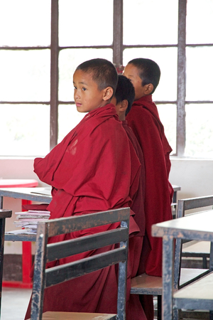 monastic: Sikkimese Buddhist children in traditional robes are attending a lesson in the classromm at the Labrang Gompa monastic school, Sikkim, India. The Labrang Gompa is a octagonal shape gompa along the road to Gagtok. The gompa was built as Buddhist ecclesiast Editorial