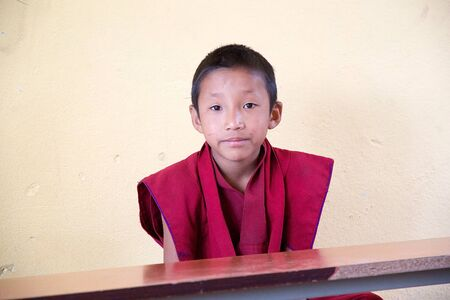 monastic: Sikkimese Buddhist child in traditional robes in the classroom at the Labrang Gompa monastic school, Sikkim, India. The Labrang Gompa is a octagonal shape gompa along the road to Gagtok. The gompa was built as Buddhist ecclesiastical fortification.