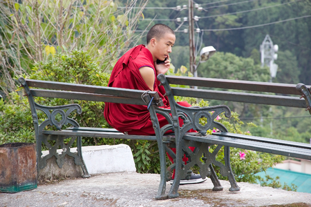 sectarian: Buddhist monk in traditional robes is calling by cellular phone at the Rumtek Monastery, Sikkim, India. Rumtek Monastery is a gompa located near gangtok, capital of Indian state of Sikkim. It is a focal point of the sectarian tensions within the Karma Kan