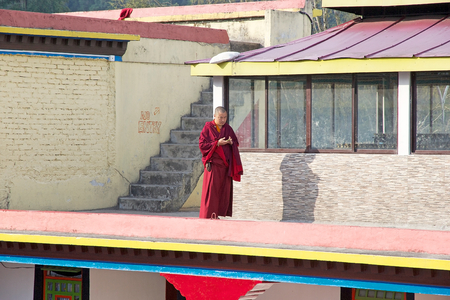 sectarian: Buddhist monk with cellular phone at the Rumtek Monastery, Sikkim, India. Rumtek Monastery is a gompa located near gangtok, capital of Indian state of Sikkim. It is a focal point of the sectarian tensions within the Karma Kangyu school of Tibetan Buddhism Editorial