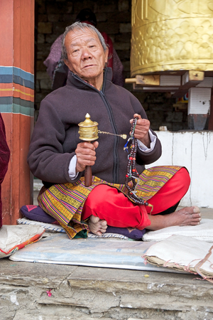 conceived: Bhutanese woman is praying with prayer wheel and prayer beads at the Memorial Chorten, Thimphu, Bhutan. The Memorial Chorten was conceived by Thinley Norbu, according to the Nyingma tradition of Tibetan Bhuddism. It was erected in 1974 in memory of Jigme  Editorial