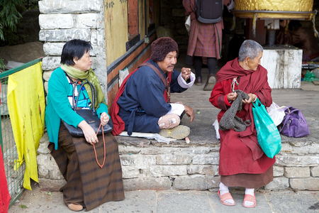conceived: Bhutanese people in traditional dress at the Memorial Chorten, Thimphu, Bhutan. The Memorial Chorten was conceived by Thinley Norbu, according to the Nyingma tradition of Tibetan Bhuddism. It was erected in 1974 in memory of Jigme Dorji Wanchuck, 3rd Druk