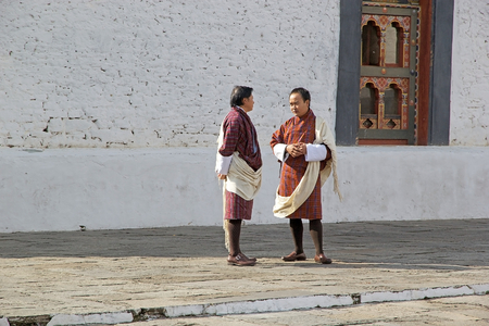 introduced: Bhutanese men are wearing the gho, the traditional and national dress in Bhutan, and the kabney, a silk scarf worn as part of the gho, both introduced in 17th century, in the courtyard at the Trashi Chhoe Dzong, Thimphu, Bhutan