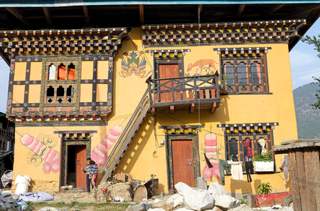 phallus: Traditional bhutanese house with multi-colored wood frontages, small arche windows and phallus symbol, Garuda and deer depicted on the facade at the Sopsokha village, Punakha, Bhutan. Phallus in Bhutan is a esoteric symbol. Traditionally symbol of an erec Editorial